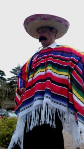 An actor dressed in traditional Mexican attire poses for a picture
