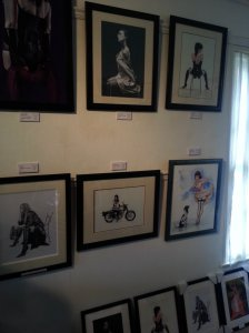"Smaller artworks desplayed on a wall. Two paintings in the upper row are entitled ""Silk lady"" and ""Naughty chair"""