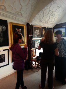 Visitors talking to Karl's assistant about his paintings