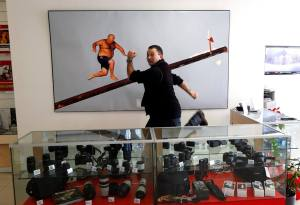 Photographer Darrin Zammit Lupi posing next to his photo at Avantech offices, February 24, 2014