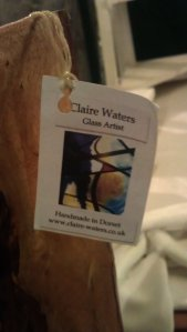 Claire Water's card attached to one of her artworks