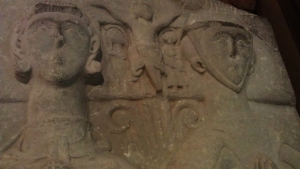 Heads of Christina and Walter. Christina is laying on the right and her long hair are hidden under head-wear known as barbette. Walter is laying on the right holding a crucifix