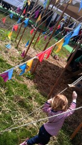 A child is leaning against Hay Fever tent waiting for his turn to roll in real hay