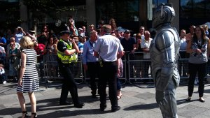 Police officer is warning the Cyberman to behave