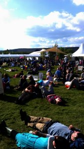 Public is sunbathing  in the lounge area in front of  the festival's bookstore