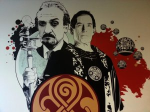 "Doctor Who Experience is decorated  with excellent murals - sorry but we don't know the artist's name. This one shows Rassilon (as played by Timothy Dalton), The Master (as played by Anthony Ainley) and Toclafane (as seen in the episode ""The Sound of Drums). The mural  also includes the official Rassilon's seal from Gallifrey."