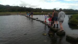 People crossing the Ewenny river using the ancient stepping stones