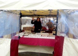 Rita Dabrowicz waving at the camera at our stand in the rain.