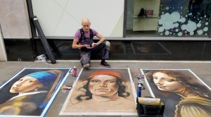 Street artist Richard Price inspects his paintings on High Street, Worcester